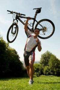 Motivationtrainer Rosario Battaglia hebt sein Mountainbike mit einer Hand in die Luft