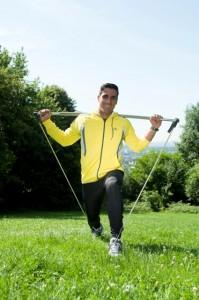 Bewegungsexperte Rosario Battaglia zeigt in der freien Natur eine einbeinige Kniebeuge mit dem Gymstick